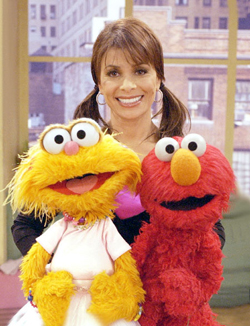 Paula Abdul poses with Zoe and Elmo from Sesame Street
